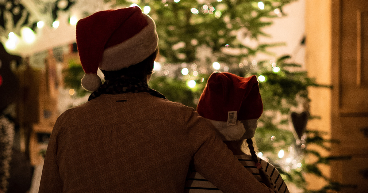 Parent And Child Sitting Before A Christmas Tree